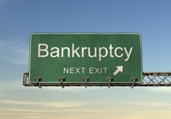 "A highway exit sign, marked ""Bankruptcy, Next Exit""."